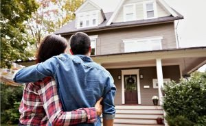 Couple looking at home after they sold it for cash