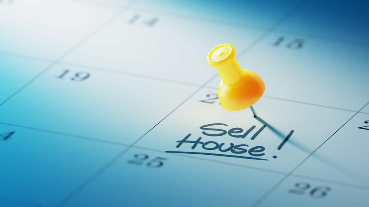 "Thumbtack on calendar notebook with words ""sell house!"""